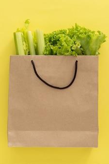 Arrière-plan de livraison d'aliments sains. nourriture végétarienne végétalienne dans des sacs en papier légumes sur fond jaune. épicerie supermarché alimentaire et concept d'alimentation propre. vue de dessus. place pour le texte. vertical