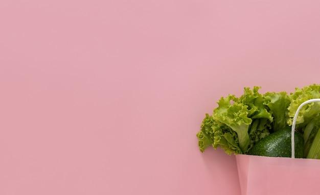 Arrière-plan de livraison d'aliments sains. nourriture végétarienne végétalienne dans des sacs en papier légumes sur fond rose. épicerie supermarché alimentaire et concept d'alimentation propre. vue de dessus. place pour le texte
