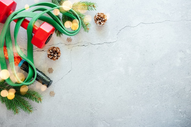 Arrière-plan de remise en forme du nouvel an avec des haltères, une bande de résistance, des branches d'arbres de noël et des lumières de noël bokeh
