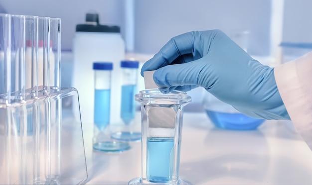 Arrière-plan scientifique ou médical avec verre glissé microscopique de la main gantée