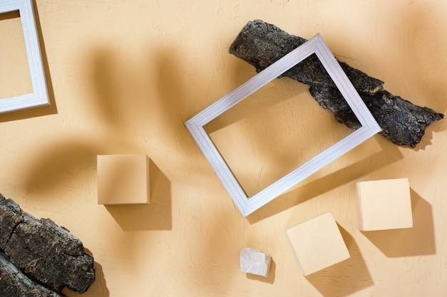 Arrière-plan de style de vie abstrait moderne : béton, cadres photo vierges, pierres et écorce d'arbre à l'ombre des feuilles. vue de dessus. place pour le texte