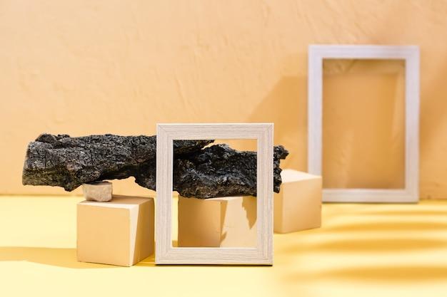 Arrière-plan de style de vie abstrait moderne : carton jaune, plâtre, cadres photo vierges, pierres, écorce d'arbre et ombre de feuille. place pour le texte