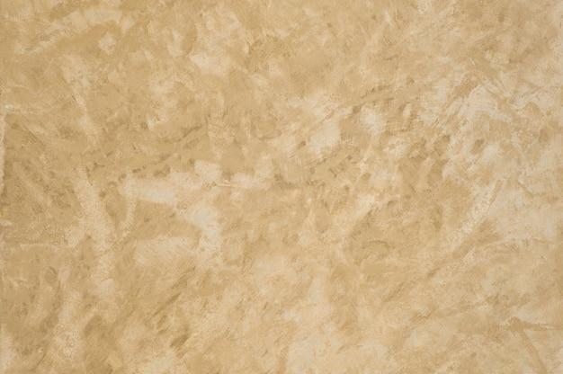 Arrière-plan de la texture plâtrée avec une couleur or effet marbre. fond artistique fait main