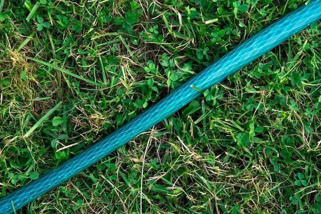 Arrière-plan avec un tuyau d'arrosage de jardin allongé sur l'herbe verte en été close up
