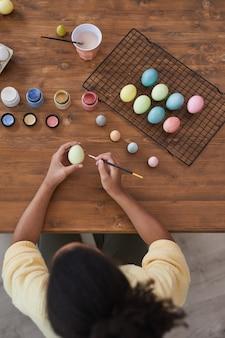 Arrière-plan vertical de la vue de dessus d'une fille afro-américaine peignant des œufs de pâques de couleur pastel sur une table en bois, décorations de pâques bricolage, espace de copie