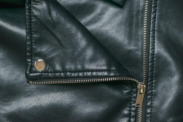 L'arrière-plan d'une veste en cuir déboutonnée avec des rivets en métal. mise à plat.