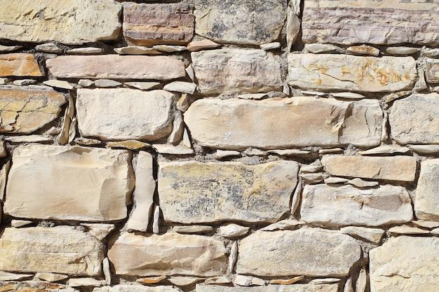 Arrière-plan, vieux mur de blocs de pierre empilés de différentes formes avec des arêtes vives.