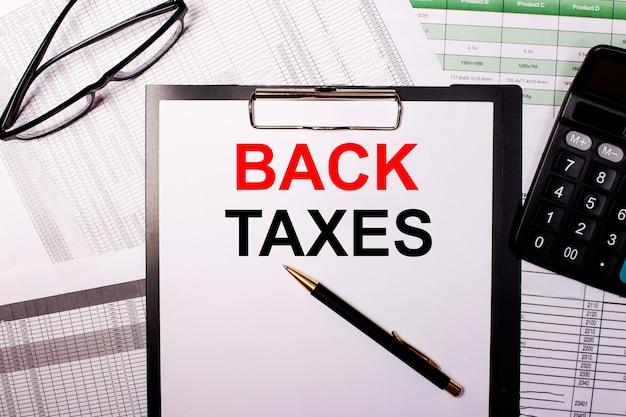 Arrière-taxes est écrit sur une feuille de papier blanc, près des verres et de la calculatrice