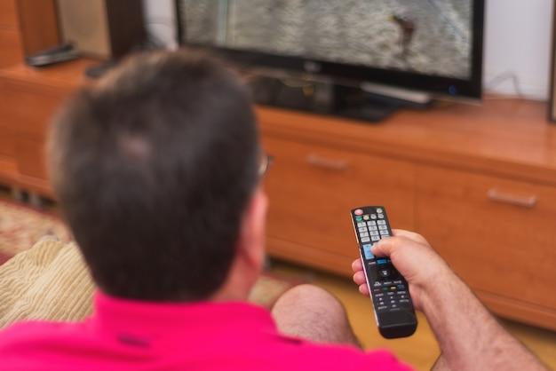 Arrière, vue, de, homme aîné, regarder, tv, tenue, télécommande