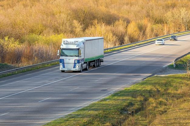 Arrivée d'un camion blanc sur la route dans un paysage rural au coucher du soleil