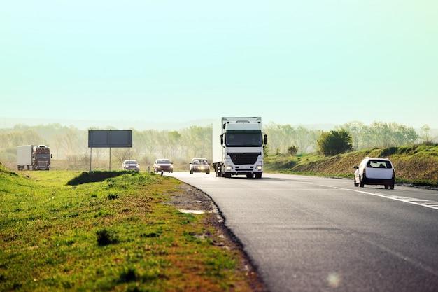 Arrivée camion blanc sur la route dans un paysage rural au coucher du soleil