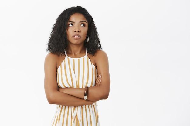 Arrogant et impatient jeune femme afro-américaine attrayante en salopette rayée jaune tenant les bras croisés sur la poitrine en levant les yeux