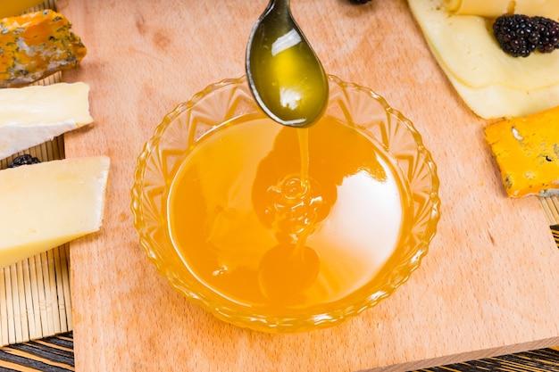 Arroser de miel doré biologique frais d'une cuillère dans un bol sur un plateau de fromages assortis à utiliser comme trempette, vue grand angle