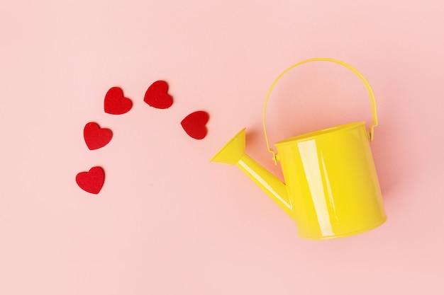 Arrosoir avec des coeurs en rose