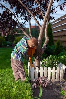 Arrosoir enfant arrosant un arbre dans l'arrière-cour