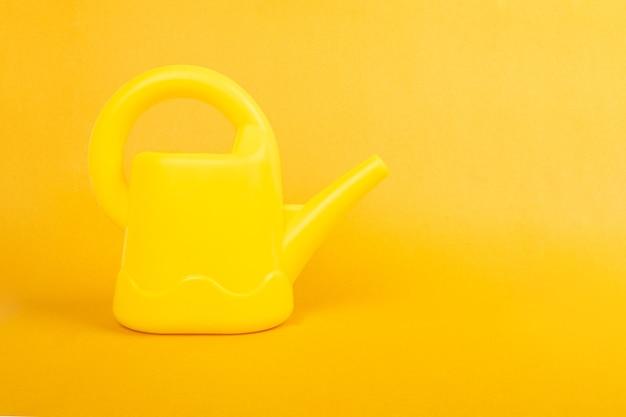 Arrosoir sur fond jaune avec espace de copie.