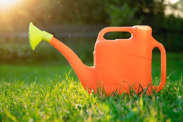 Arrosoir orange en plastique sur l'herbe verte dans le jardin rétroéclairé par les rayons du soleil couchant