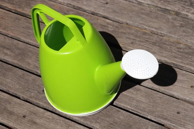 Un arrosoir en plastique vert.