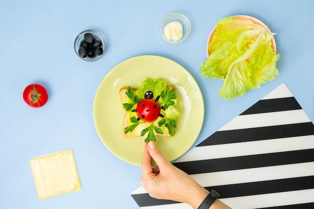 Art alimentaire amusant pour les enfants. sandwich coccinelle sur mur bleu. comment préparer un petit-déjeuner créatif pour un enfant à la maison. instructions étape par étape, vue de dessus.