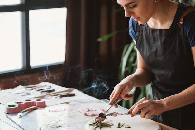 Art de l'argile. artisanat en céramique. ambiance de studio d'artiste créatif. femme avec des outils de modélisation sur le lieu de travail. fumée d'encens.