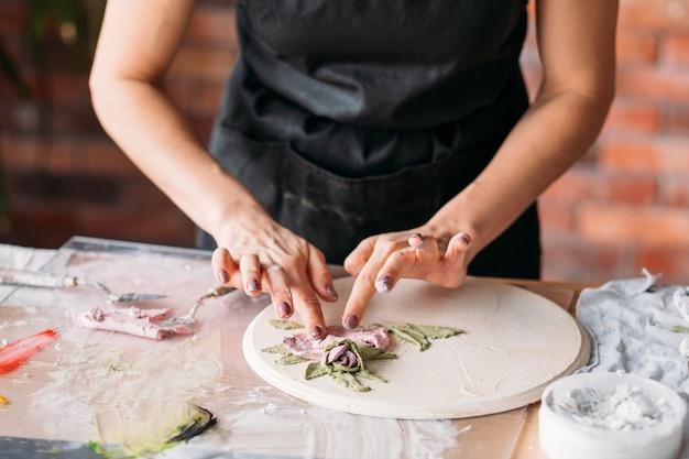 Art de l'argile. artisanat en céramique. ambiance de studio d'artiste créatif. femme avec des outils de modélisation sur le lieu de travail.