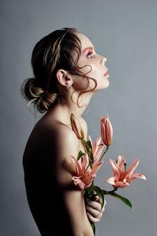 Art beauté fille visage agrandi avec des lis dans les mains