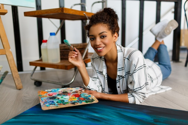 Art contemporain. talent et créativité. inspiré de la jeune femme noire travaillant sur ses illustrations abstraites de l'océan.