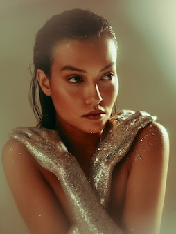 Art corporel étincelant d'argent, jeune femme aux cheveux mouillés et maquillage parfait festif qui pose en studio