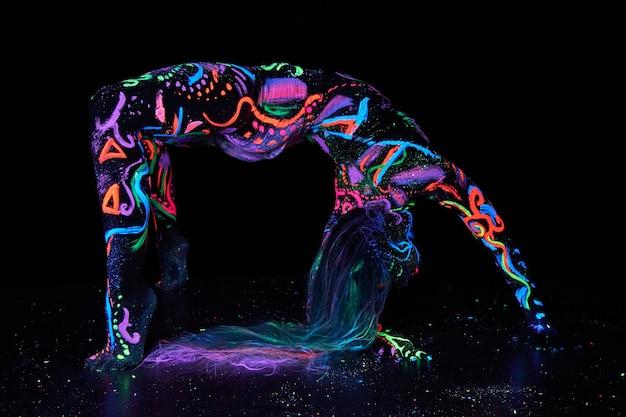 Art corporel femme art sur le corps dansant dans la lumière ultraviolette