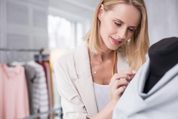 Art de la couture. heureux créateur féminin fixant le tissu tout en regardant vers le bas