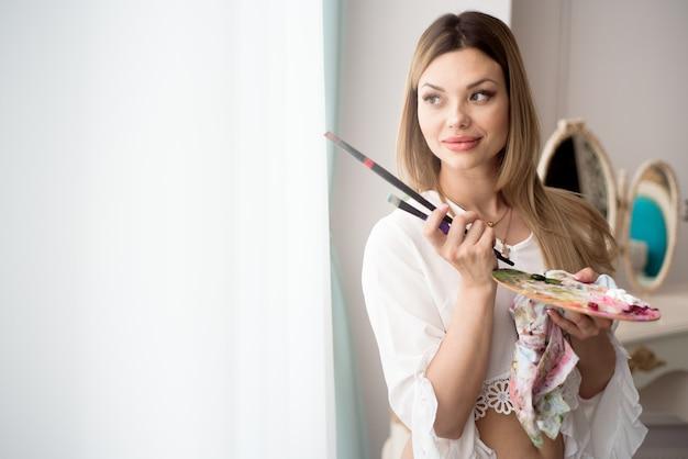 Art, créativité, emploi et concept d'occupation créative. artiste féminine posant devant la fenêtre et peinture à l'huile ou à la peinture acrylique