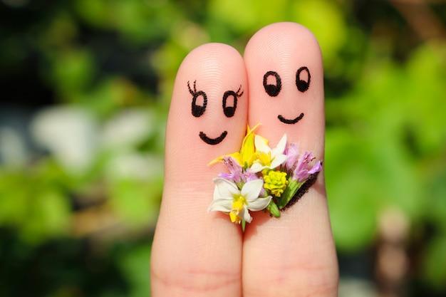 Art de doigt d'un couple heureux. l'homme donne des fleurs à une femme.