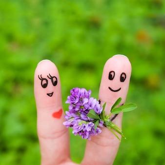 Art de doigt d'un couple heureux. l'homme offre des fleurs à une femme.