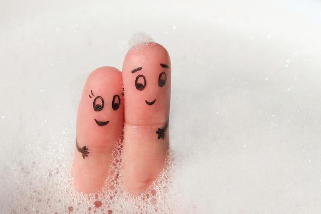 Art de doigt du couple heureux se baigner dans le bain avec de la mousse.