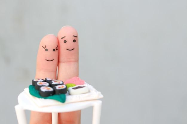 Art de doigts de couple heureux. l'homme et la femme mangent des sushis au café.