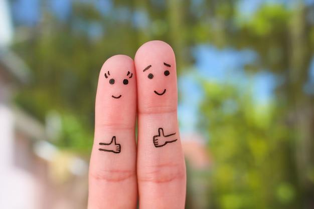 Art des doigts de couple heureux montrant les pouces vers le haut.