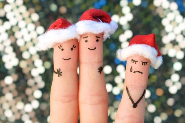 Art de doigts de couple heureux riant dans des chapeaux de père noël. la femme est en colère et jalouse. l'art des doigts du couple fête noël.