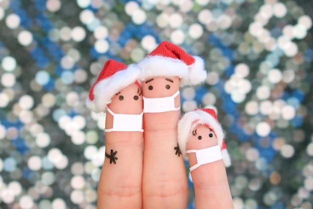 L'art des doigts de la famille dans un masque médical de covid-2019 célèbre noël. concept de personnes en chapeaux de nouvel an.