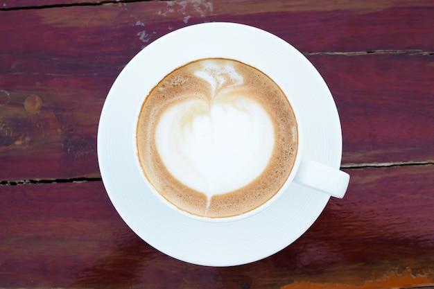 Art du café au lait chaud dans une tasse blanche sur une table en bois