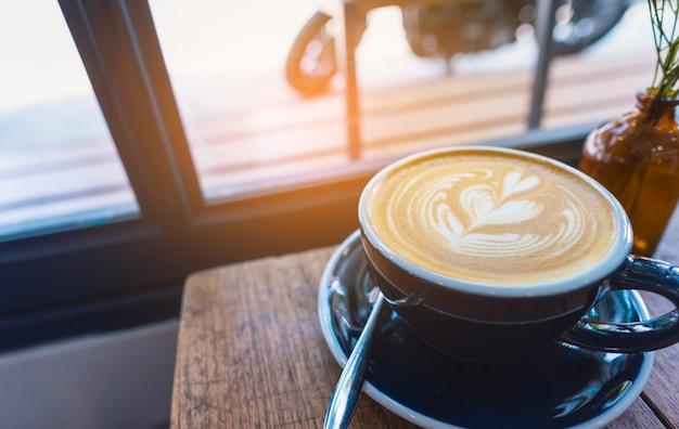 Art du café latte dans une tasse sur la table en bois.