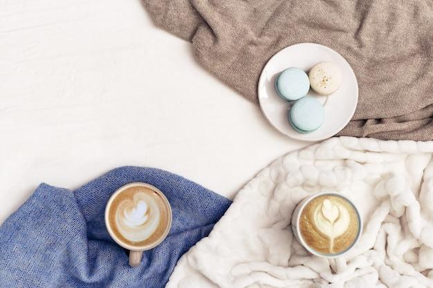 Art du cappuccino du café du matin dans une grande tasse et traiter les macarons dessert pour deux personnes. café fait maison pour le petit déjeuner dans un cadre confortable. concept de détente d'hiver. vue de dessus.