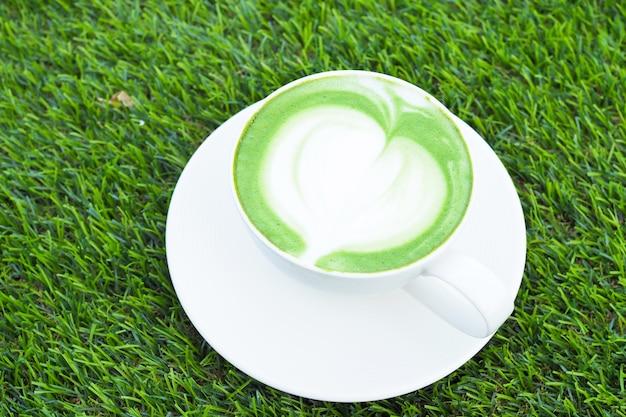 Art du thé vert chaud matcha latte dans une tasse blanche sur fond d'herbe verte