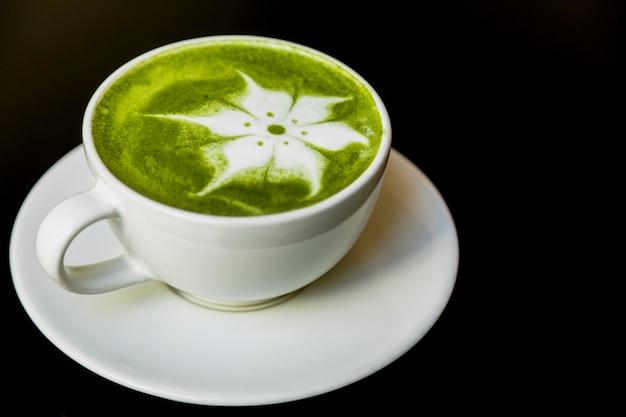 Art de la fleur de latte avec thé vert japonais matcha dans une tasse sur fond noir