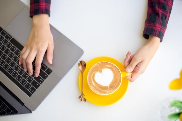 Art latte chaud dans une tasse jaune sur le bureau de travail