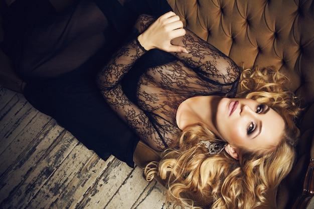 Art mode portrait d'une belle jeune femme blonde élégante avec massive boucles d'oreilles scintillantes, maquillage et coiffure dans une robe de dentelle noire posant sur une vue de dessus de canapé classique brun