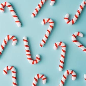 Art de noël minimaliste créatif. modèle fait avec des bonbons de noël sur fond bleu clair. mise à plat. copiez l'espace. composition minimale.