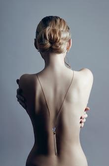 Art nude fashion femme blonde au dos nu sur fond gris