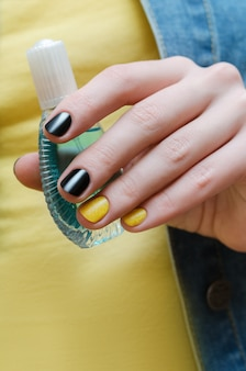 L'art des ongles. belle main féminine avec manucure noir et jaune