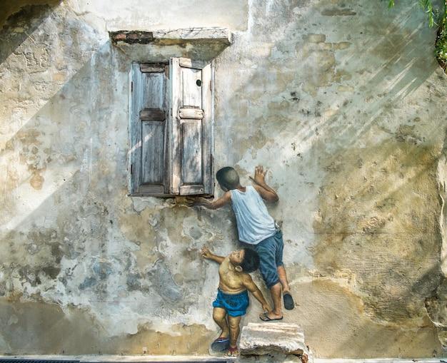 Art de la rue 3d sur le mur. des tableaux de garçons jouent près de la fenêtre.