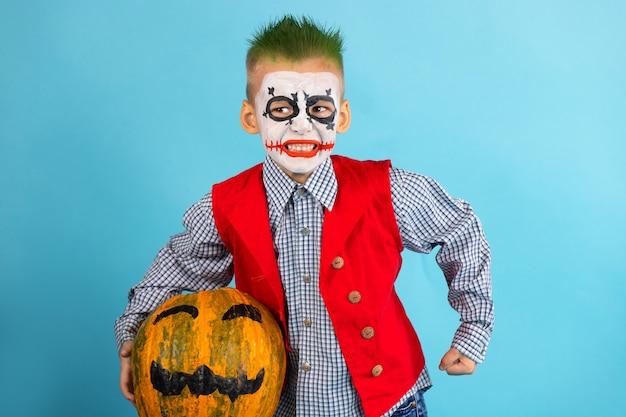 Art de visage d'halloween et cheveux verts. l'enfant tient une citrouille orange dans les mains. concept d'enfants halloween. .